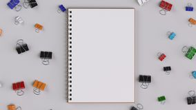 Blank spiral notebook with colorful binder clips on white table. Business, education or office mockup. 3D rendering illustration Royalty Free Stock Photos