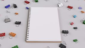 Blank spiral notebook with colorful binder clips on white table. Business, education or office mockup. 3D rendering illustration Stock Image