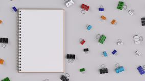 Blank spiral notebook with colorful binder clips on white table Royalty Free Stock Photos