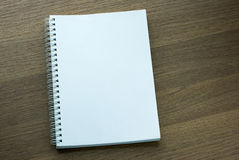 Blank spiral notebook on dark wood background Stock Images