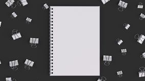 Blank spiral notebook with white binder clips on black table. Business, education or office mockup. 3D rendering illustration Stock Photo