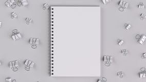 Blank spiral notebook with white binder clips on white table. Business, education or office mockup. 3D rendering illustration Royalty Free Stock Photos