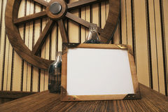Blank square frame. Leaning on bottles, with wheel on wall in the background. Mock up, 3D Render Royalty Free Stock Photo
