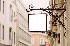 Blank square signboard, hanging from wrought iron bracket Royalty Free Stock Photo