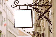 Blank square signboard, hanging from wrought iron bracket Stock Photos