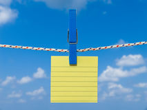 Blank square of yellow paper suspended from a washing line. Stock Photos