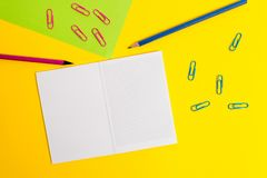 Blank squared notebook colored paper sheet clips pencils highlighters markers ballpoint plain color background. Empty stock photo