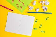 Blank squared notebook colored paper sheet crushed balls clips pencils highlighters markers ballpoint plain color stock photography