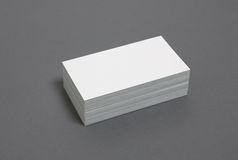 Blank stacked up business cards. Blank business cards stacked up on a grey background Stock Photos
