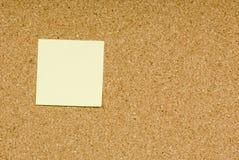 Blank sticky note. On a cork bulletin board royalty free stock image