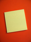 Blank Sticky Note. A blank yellow note on red background. Add your own message Stock Photography