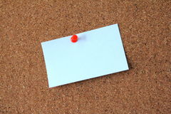 BLank sticky note. On corkboard with red pin Royalty Free Stock Photo