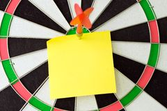 Blank sticky note on dartboard with dart stock photography