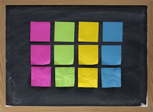 Blank sticky notes on blackboard Royalty Free Stock Images