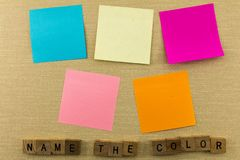Blank sticky notes name color. Name the color of postit sticky notes on bulletin education school board learning colors block wooden scabble letters Royalty Free Stock Photos