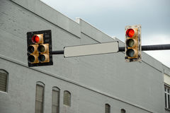 Blank Street Sign With Red Light. Two red traffic lights with a building and a cloudy sky Royalty Free Stock Photos