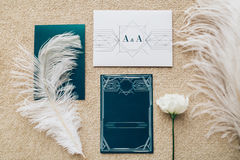 Blank stylized romantic invitation on carpet background. Top view. Blank stylized with dark turquoise card romantic invitation on peach carpet background. Top Royalty Free Stock Image