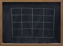 Blank table on blackboard Stock Images