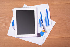 Blank tablet with business chart and pen on wooden table Royalty Free Stock Photography