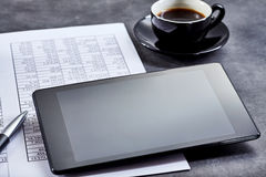 Blank tablet on a business spreadsheet Royalty Free Stock Images