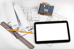 Blank tablet and house scale model on architectural blueprints Royalty Free Stock Image