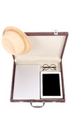 Blank tablet, laptop glasses and hat in briefcase Royalty Free Stock Photography