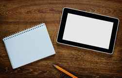Blank tablet and notebook on a wooden table Stock Image