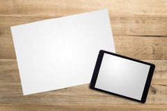 Blank tablet and opened magazine pages lying on wood Stock Image