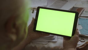 A blank tablet PC in landscape orientation with a green screenin hands. 4k stock video