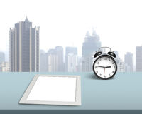 Blank tablet with retro alarm clock on desk Royalty Free Stock Photography