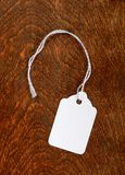 Blank Tag. Blank white tag with a string on a wood table top Royalty Free Stock Photo