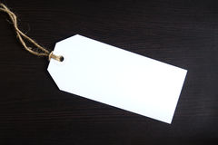 Blank tag. Blank white tag on dark wooden background Royalty Free Stock Images