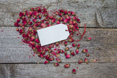 Blank tag on heart made of dried flowers and buds of roses Stock Image