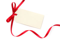 Blank Tag with Red Ribbon. Blank gift tag tied with a bow of red satin ribbon.  Isolated on white, with soft shadow Stock Photo