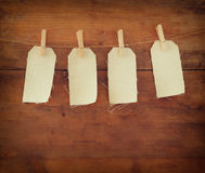 Blank tags hanging on wooden background Royalty Free Stock Photos