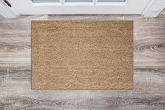 Free Blank Tan Colored Coir Doormat Before The White Door In The Hall. Mat On Wooden Floor, Product Mockup Royalty Free Stock Photos - 108546258