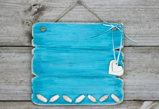 Blank teal blue sign with seashells and hearts hanging on rustic wooden door Royalty Free Stock Image