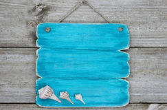 Blank Teal Blue Sign With Seashells Hanging On Rustic Wooden Door Stock Photos