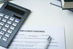 Employment Agreement with pen and calculator Stock Photos