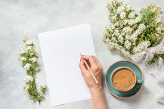 Blank for text, morning black coffee, and bouquet white spring flowers. Top view. Spring. Female hand writing. Female hand writing. Blank for text, morning black royalty free stock photography