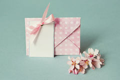 Blank thank you or greeting card and envelope And a spring flowering branch. Blank white paper card with With a pink bow under envelop On a turquoise background Stock Images
