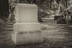 Blank tombstone in an old cemetery. Black and white photo of blank tombstone in a treed cemetery Royalty Free Stock Photography