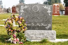 Blank tombstone in an old cemetery. Blank tombstone with wreath in a cemetery on a sunny day Royalty Free Stock Image