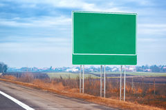 Blank traffic road sign by the roadway Royalty Free Stock Images