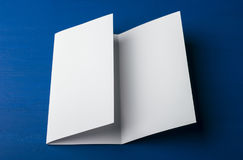 Blank tri fold brochure on blue background to replace your design or message. A mock-up for brand identification for designers Stock Photo