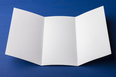 Blank tri fold brochure on blue background to replace your design or message. Royalty Free Stock Image