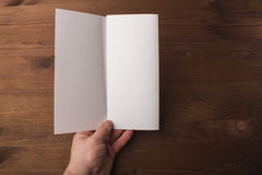 Blank tri fold brochure in hand on wooden background to replace your design or message Royalty Free Stock Images