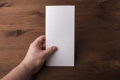 Blank tri fold brochure in hand on wooden background to replace your design or message. A mock-up for brand identification for designers Royalty Free Stock Photography