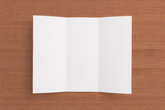 Blank tri fold brochure on wooden background. To replace your design or message Royalty Free Stock Photography