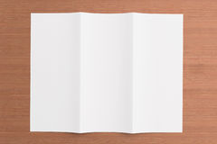 Blank tri fold brochure on wooden background. To replace your design or message Royalty Free Stock Image